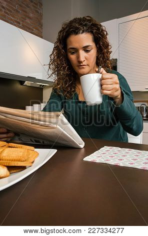 Young Woman Having Breakfast In The Kitchen And Looking The Newspaper