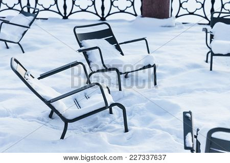 Chairs Covered With Snow Outdoor. Shot Of Metal Furniture During Winter Weather. Empty Chairs During