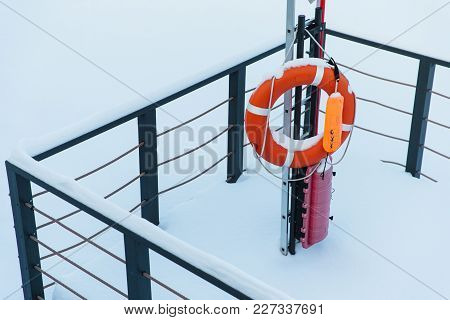Life Preserver During Winter Weather. Lifebuoy Covered With White Snow. Winter Rescue Equipment Froz