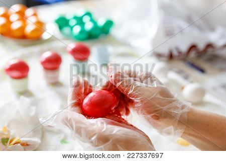 Easter, Holidays, Tradition And People Concept. Close-up Of Adult Hands Coloring Easter Eggs With Co