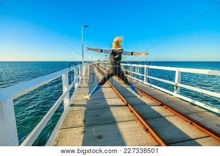 Carefree Young Sporty Woman Jumping At Busselton Jetty In Busselton, Western Australia. Happy Female