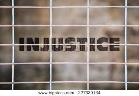 Word Injustice Written Under A Wire Fence And Blurry Background