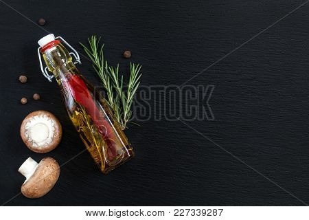 Rosemary Bunch, Mushrooms, Olive Oil With Pepper And Spices And Fragrant Pepper On Black Stone Surfa
