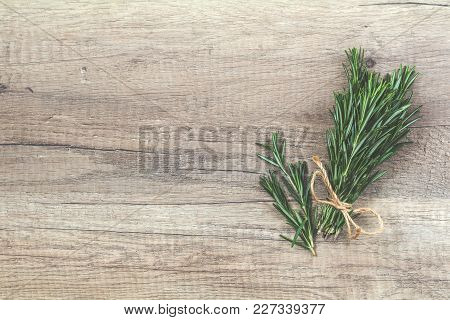 Rosemary Bunch Of Bouquets On Light Wooden Surface. Toned Photo, Top View, Copy Space.