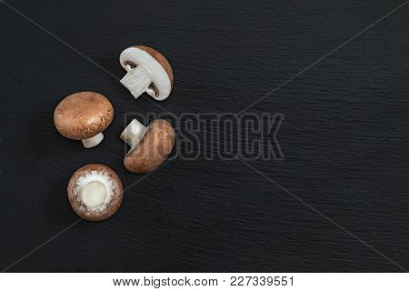 Mushrooms On Black Stone Surface. Top View, Copy Space. Fresh Raw Champignon With A Brown Cap On Dar