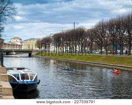 River Moika And A Boat With Canoe Boats Floating Along The River In The Center Of The City Of St. Pe