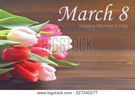 Happy Woman's Day. March 8. Tulips On A Brown Wooden Table.
