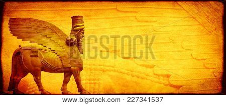 Grunge background with paper texture of yellow color and lamassu - human-headed winged bull statue, Assyrian protective deity