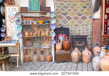 Traditional moroccan souvenirs - carpet, plates, jugs and pots made of clay, souk in Fes, Morocco, Africa