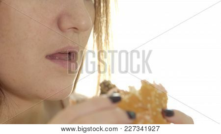 Young Woman Eating Appetizing Burger