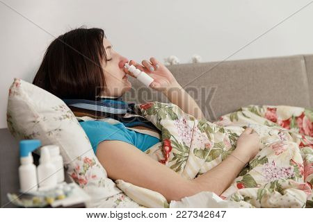 Sick Woman Lying In Bed At Home, Spray In Nose