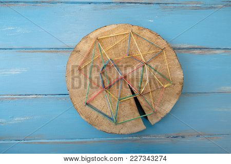 A Wooden Board With Broken Nails And Colorful Rubber Bands On A Blue Background