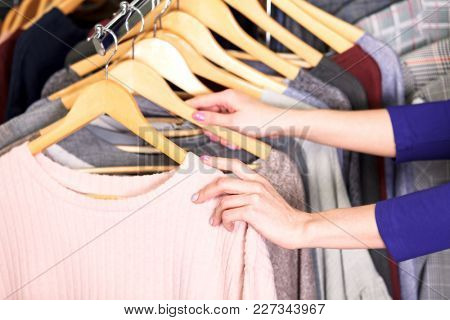 Closeup shot of hands of woman who choosing new clothes, fashion shop concept
