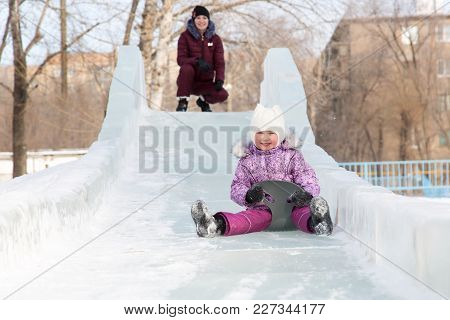 Mom And Daughter Are Riding From A Snowy Mountain.