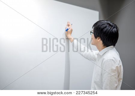 Young Asian Man Writing On White Board In Conference Room. Business Meeting Presentation Concept
