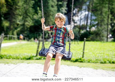 Funny Kid Boy Having Fun With Chain Swing On Outdoor Playground During Rain. Child Swinging On Warm