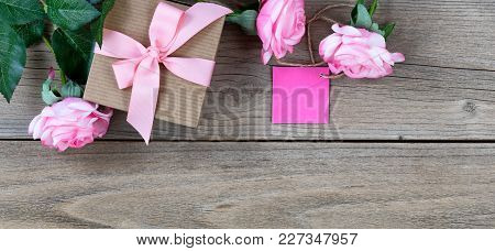 Pink Roses With Gift Box And Tag And On Weathered Wooden Boards