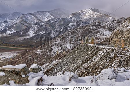 Frst Autumn Snow In The Mountains On The Pass Wiht View On The Valley, Hairpin Curve Of The Asphalt