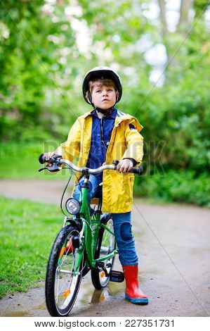 Cute Little Preschool Kid Boy Riding On Bicycle In Park. Child In Helmet, Yellow Rain Coat And Red R