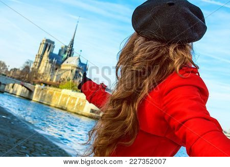 Bright In Paris. Modern Woman In Red Trench Coat On Embankment Near Notre Dame De Paris In Paris, Fr