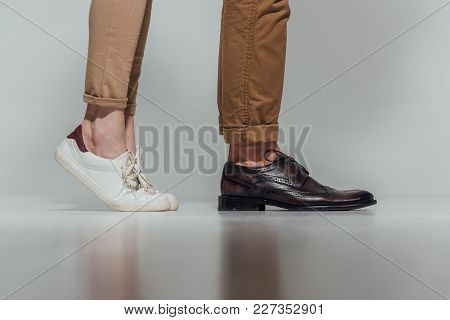 Cropped Shot Of Male And Female Legs In Footwear With Reflection On Grey