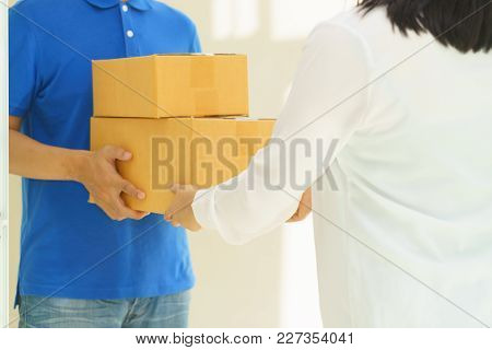 Woman Receiving Package From Delivery Man Concept.