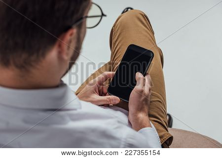 Cropped Shot Of Young Man In Eyeglasses Using Smartphone With Blank Screen Isolated On Grey