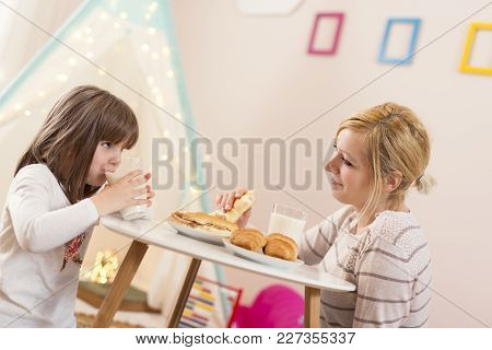 Mother And Daughter Having Breakfast In A Play Room, Eating Sandwiches And Drinking Milk