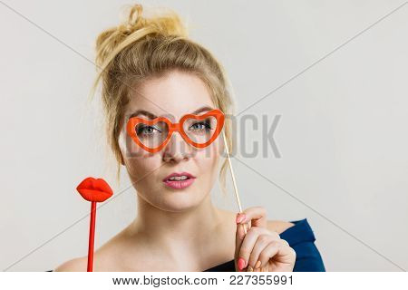 Happy Blonde Woman Holding Carnival Accessories On Stick Fake Red Lips And Paper Heart Shaped Glasse