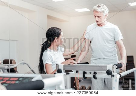 Rehabilitation. Concentrated Old Grey-haired Man Exercising On A Training Device And Talking To A Sm