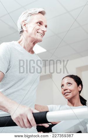 Recovery. Exuberant Energetic Old Grey-haired Man Smiling And Exercising On A Training Device And A