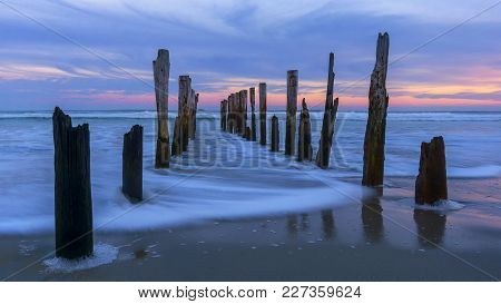 Sunrise With Abandoned Wooden Piles At St Clair Beach, Dunedin, Otago, New Zealand.