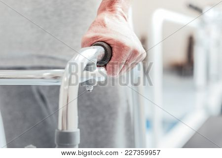 Perseverance. Old Wrinkled Masculine Hand Holding A Handle Of A Modern Metal Training Device