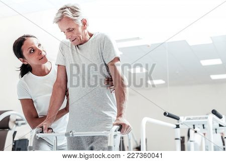 Doing His Best. Determined Old Crippled Grey-haired Man Exercising On A Training Device While A Dark