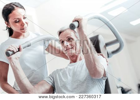I Will Succeed. Happy Old Grey-haired Man Exercising On A Training Device And A Pretty Young Smiling