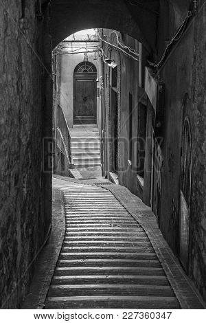 Historic Buildings Of Perugia, Umbria, Italy, At Evening. Typical Street. Black And White