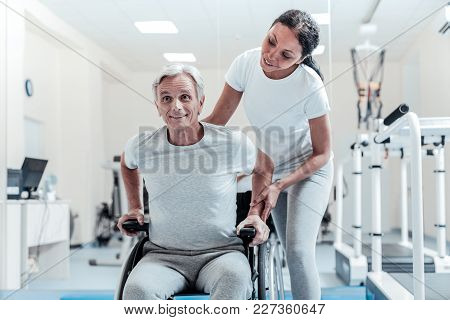 Wheelchair. Happy Smiling Old Grey-haired Man Sitting In A Wheelchair And A Cheerful Young Dark-hair