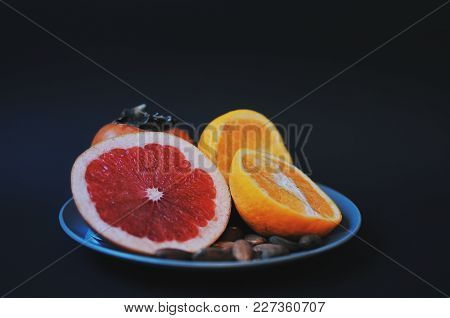 Variety Of Fruits On The Blue Plate. Grapefruit, Oranges, Persimmon And Almonds On Black Background.
