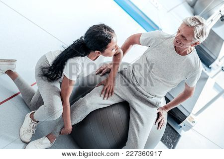 I Can Help. Smiling Old Grey-haired Man Sitting On A Ball For Exercises And A Young Dark-haired Afro