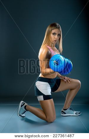 Fitness Model Holding Weights Or Dumbell On Dark Background. Sportswoman Doing Physical Exercises