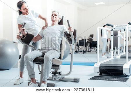 Healthy Lifestyle. Happy Old Grey-haired Man Smiling And Exercising On A Training Device And A Prett
