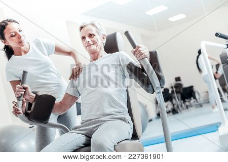 Being Vigorous. Exuberant Old Crippled Grey-haired Man Smiling And Exercising On A Training Device A