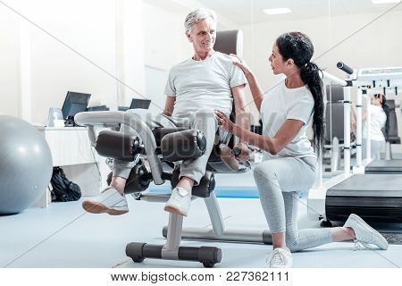 Trying His Best. Vigorous Old Crippled Grey-haired Man Smiling And Exercising On A Training Device W