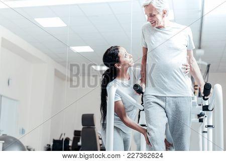 Well Done. Happy Old Wrinkled Grey-haired Man Smiling And Exercising On A Training Device While A Gl