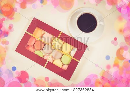 Colorful Macaroons In Gift Box And White Cup Of Coffee On Beige Background
