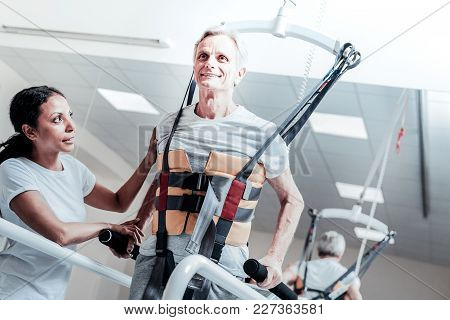 Training Muscles. Inspired Old Grey-haired Man Smiling And Exercising On A Training Device And Learn