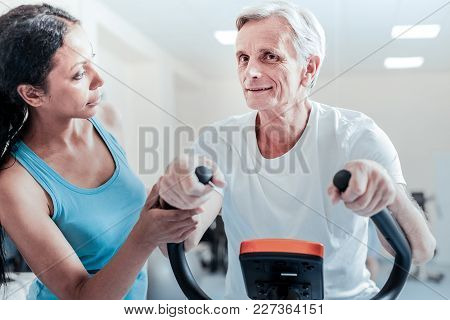 Are You Ok. Smiling Old Wrinkled Grey-haired Man Exercising On A Training Device While A Beautiful Y