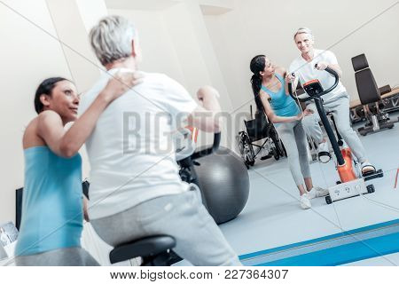 Perfect. Smiling Old Grey-haired Man Exercising On A Training Device And Looking In The Mirror While