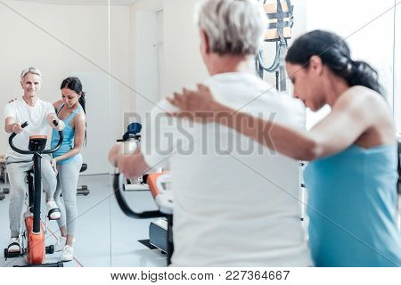 In High Spirits. Beaming Old Grey-haired Man Exercising On A Training Device And Looking In The Mirr