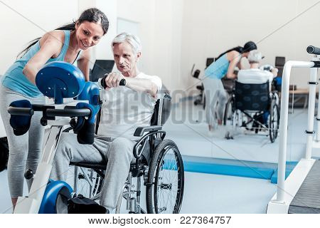 Useful Exercises. Concentrated Old Grey-haired Man Exercising On A Training Device And Sitting In A